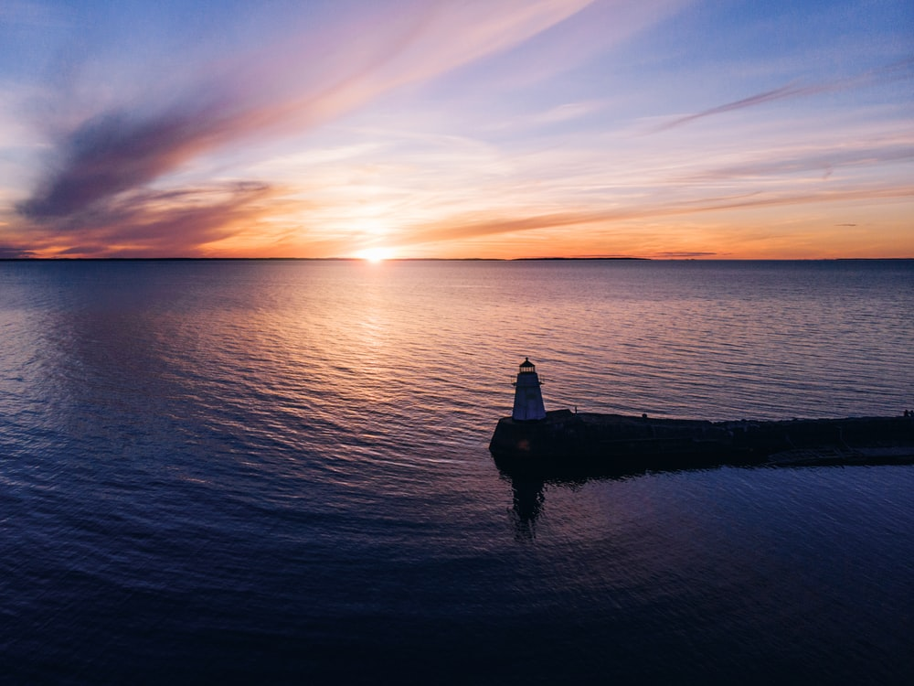 silhouette of man standing on rock in front of sea during sunset