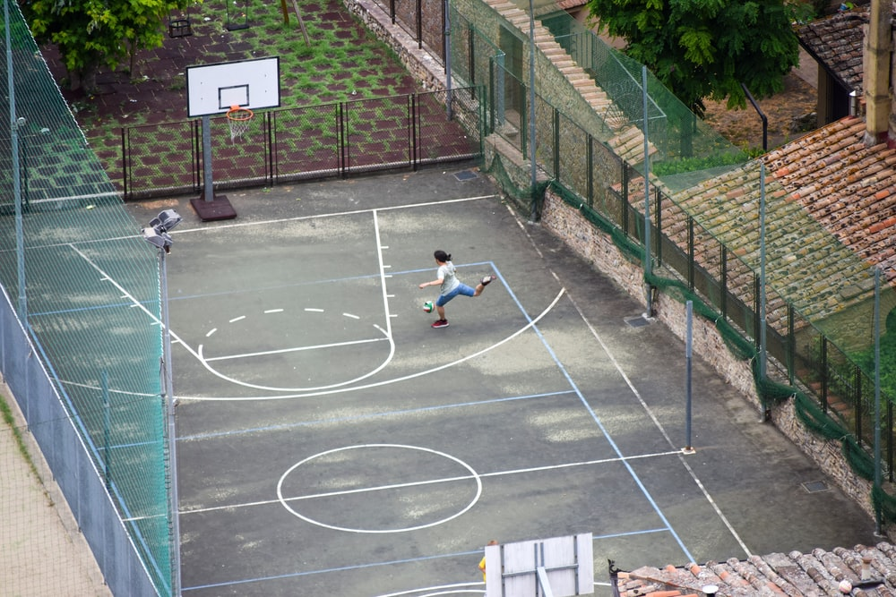 woman in white shirt sitting on basketball court during daytime