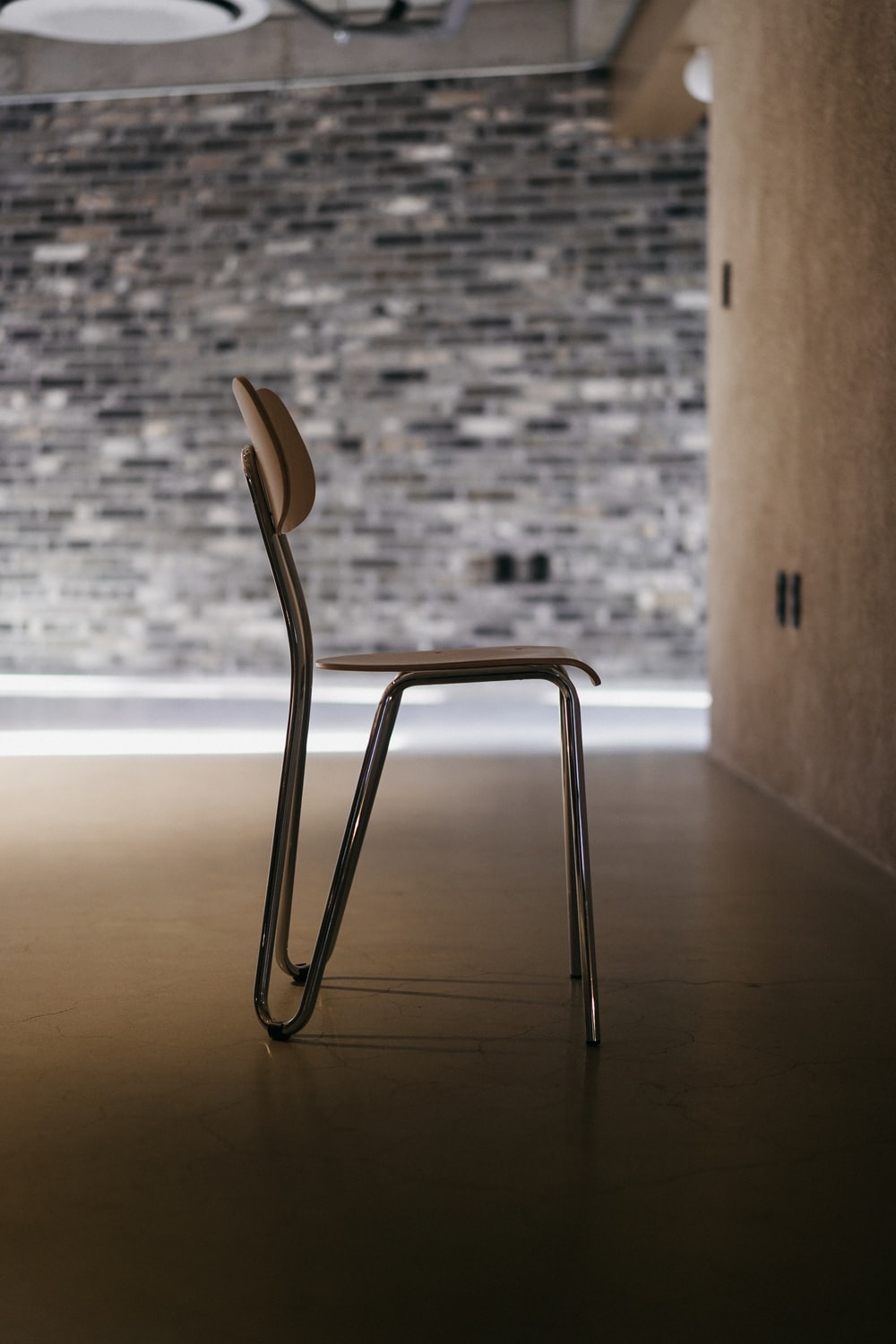 stainless steel chair beside brown wooden wall