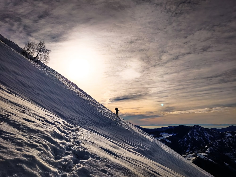 person standing on snow covered mountain during sunset