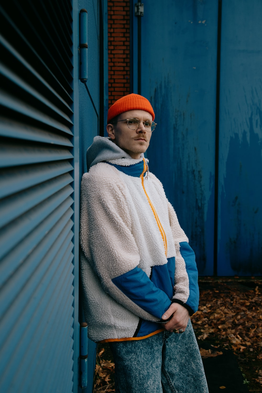 man in white and blue hoodie wearing red knit cap standing beside blue wall