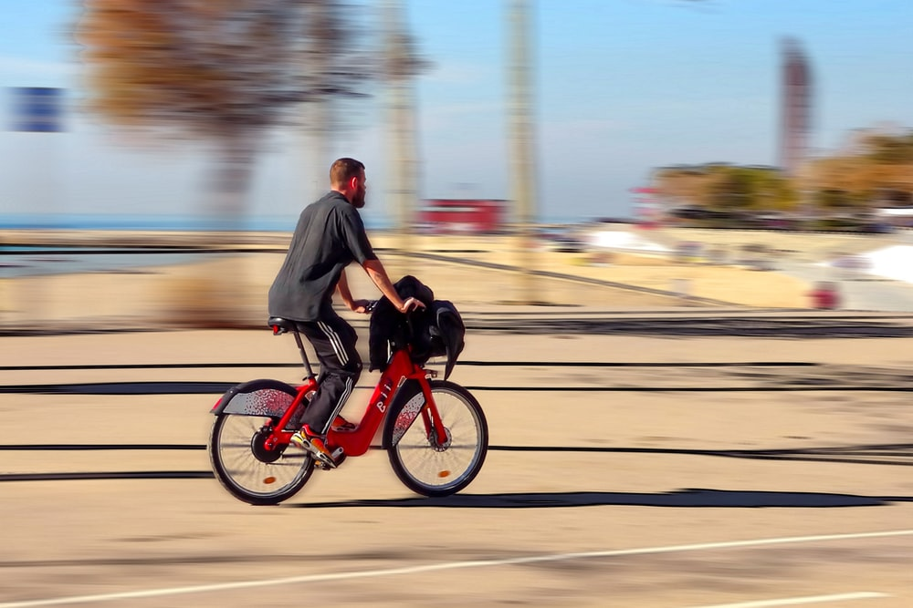 man in black jacket riding red motorcycle on road during daytime