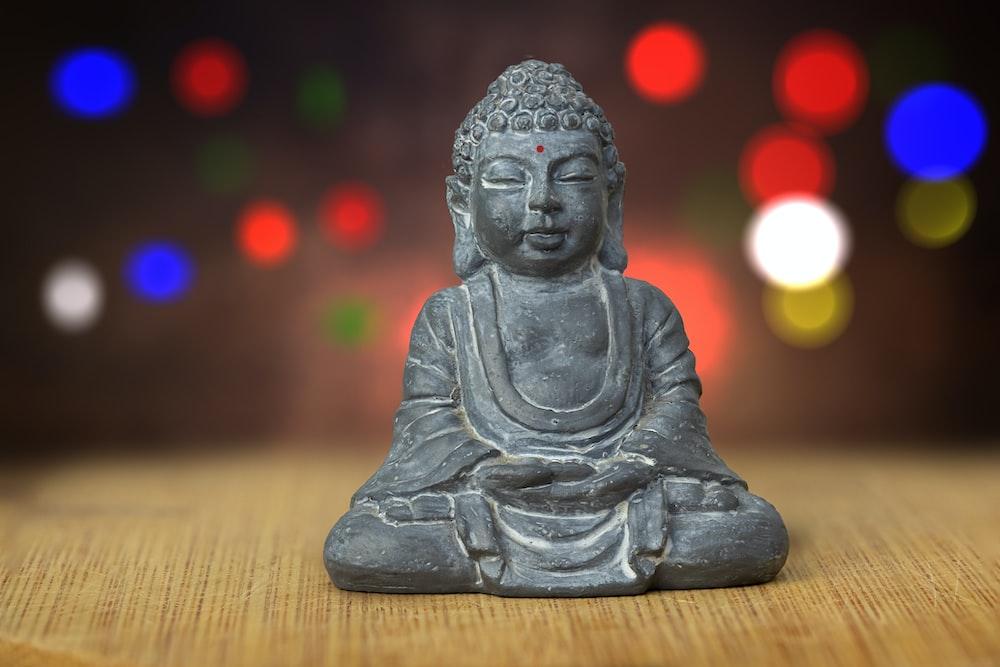 gray ceramic buddha figurine on brown wooden table