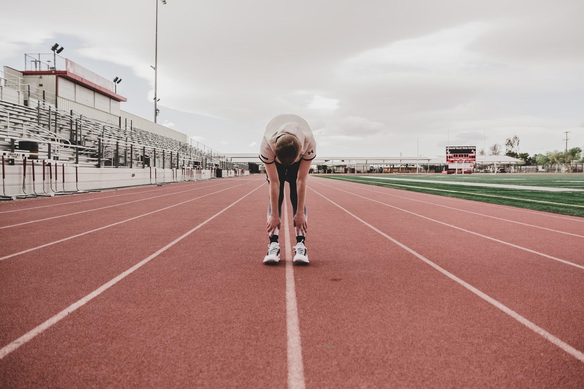 Atleta sozinho alongando em uma pista de atletismo.