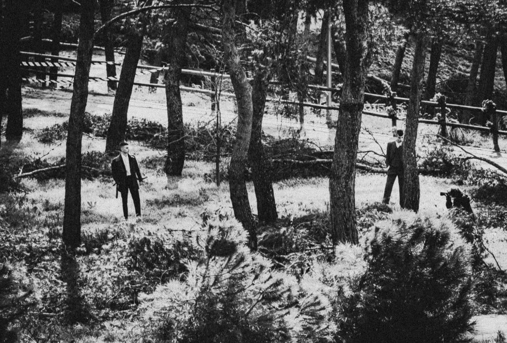 grayscale photo of 2 person standing near trees