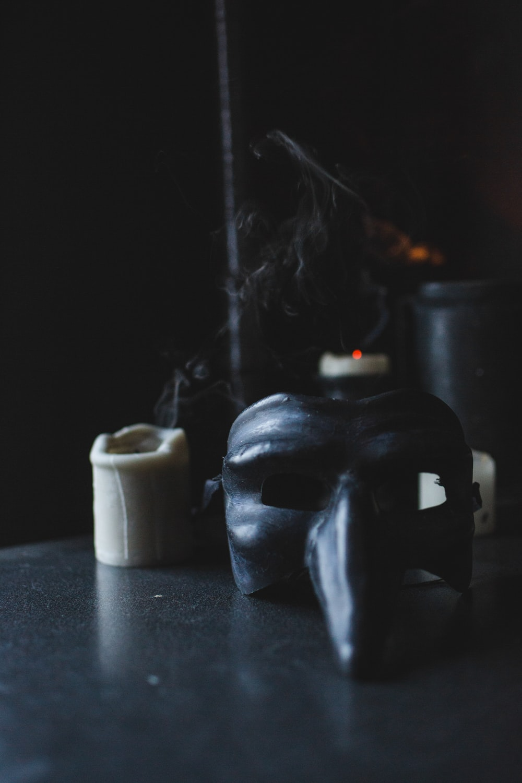 black skull candle holder beside white pillar candle
