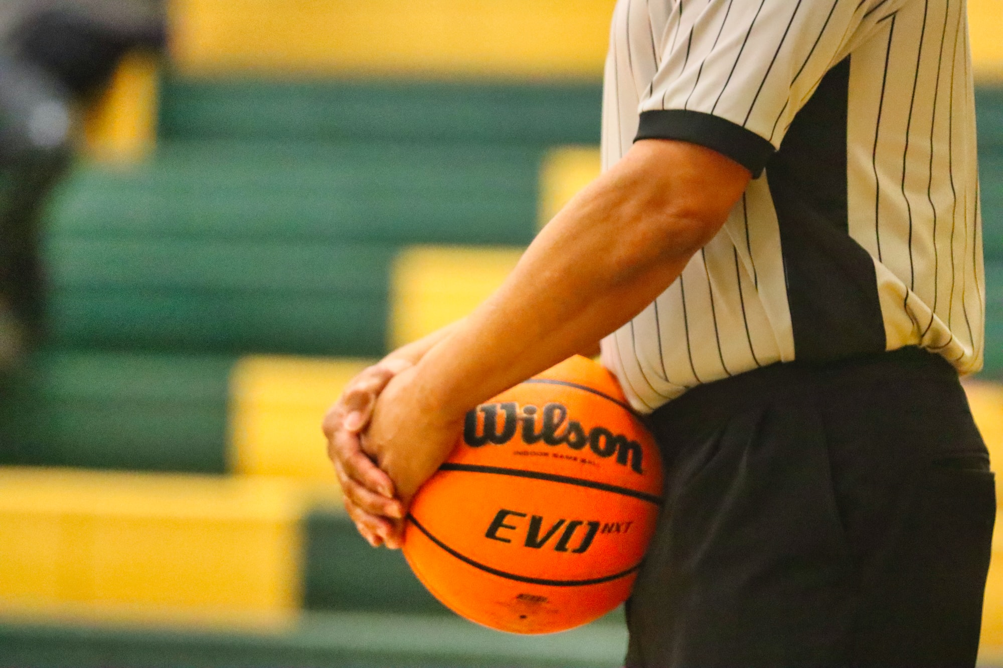 Basketball referee holds on to the basketball during the timeout of a high school basketball game in Pittsboro, North Carolina.