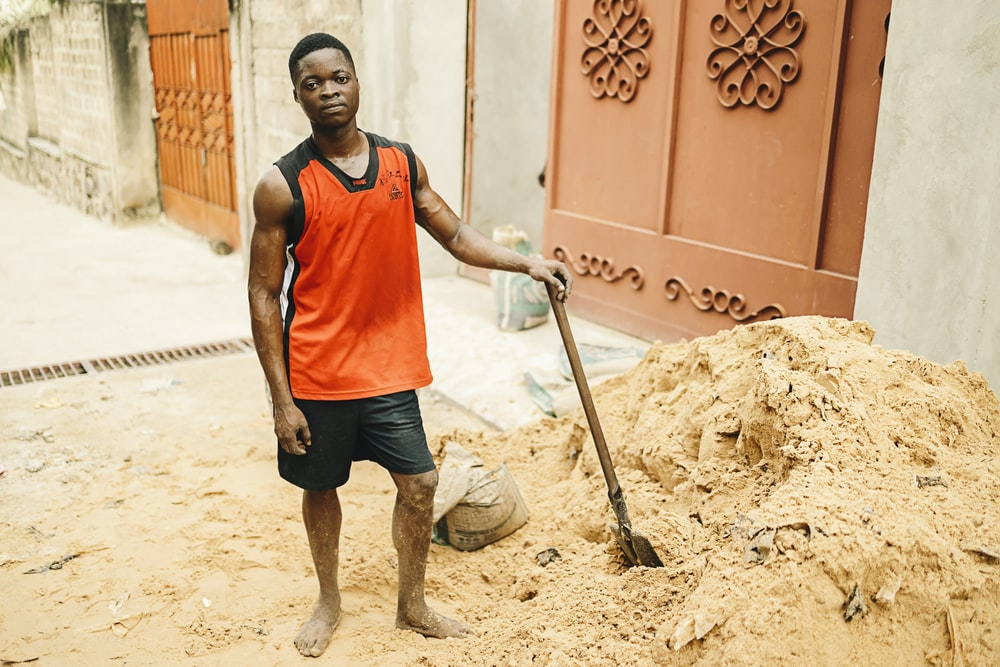 man in red tank top and black shorts holding shovel