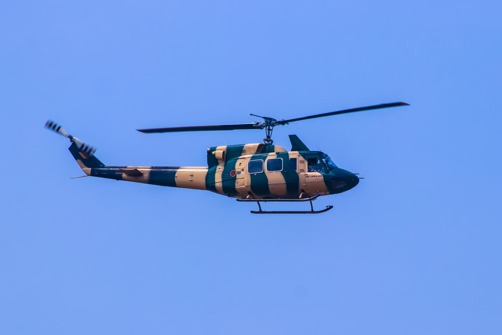 orange and black helicopter flying in the sky