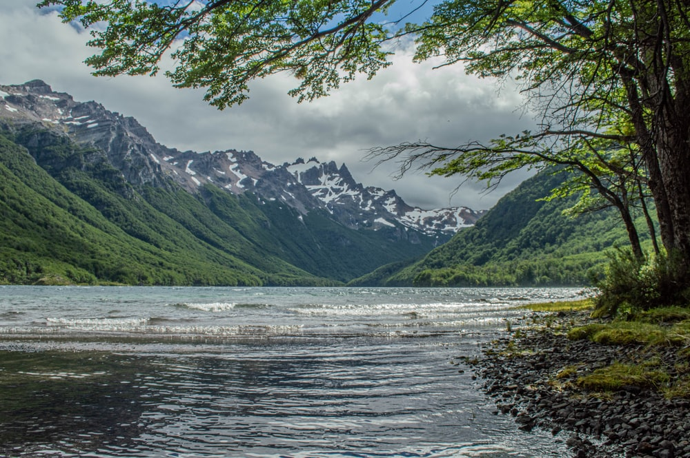 green and white mountains beside body of water under white clouds during daytime