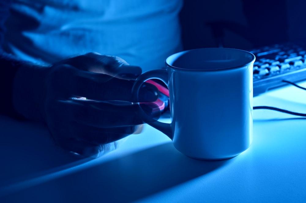 white ceramic mug on blue table