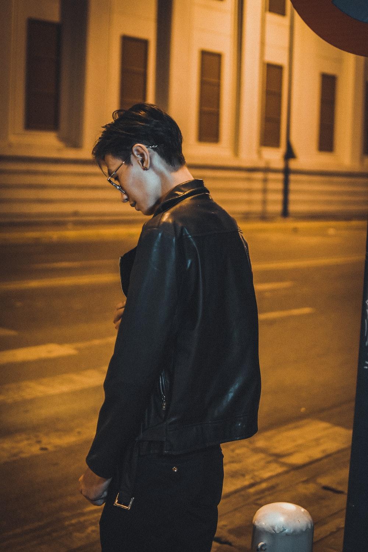 man in black coat standing on the sidewalk