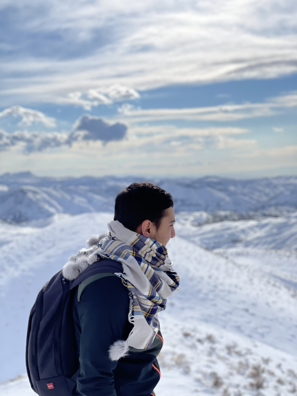 man in black jacket carrying backpack on snow covered mountain during daytime