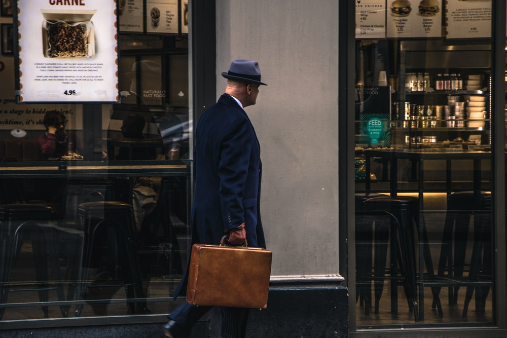 man in black suit jacket and blue hat standing in front of store