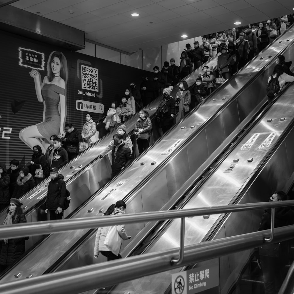 grayscale photo of people in a escalator