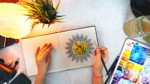 person holding white and green flower painting