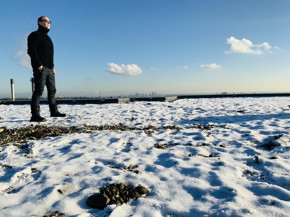 man in black jacket standing on snow covered field under blue sky during daytime