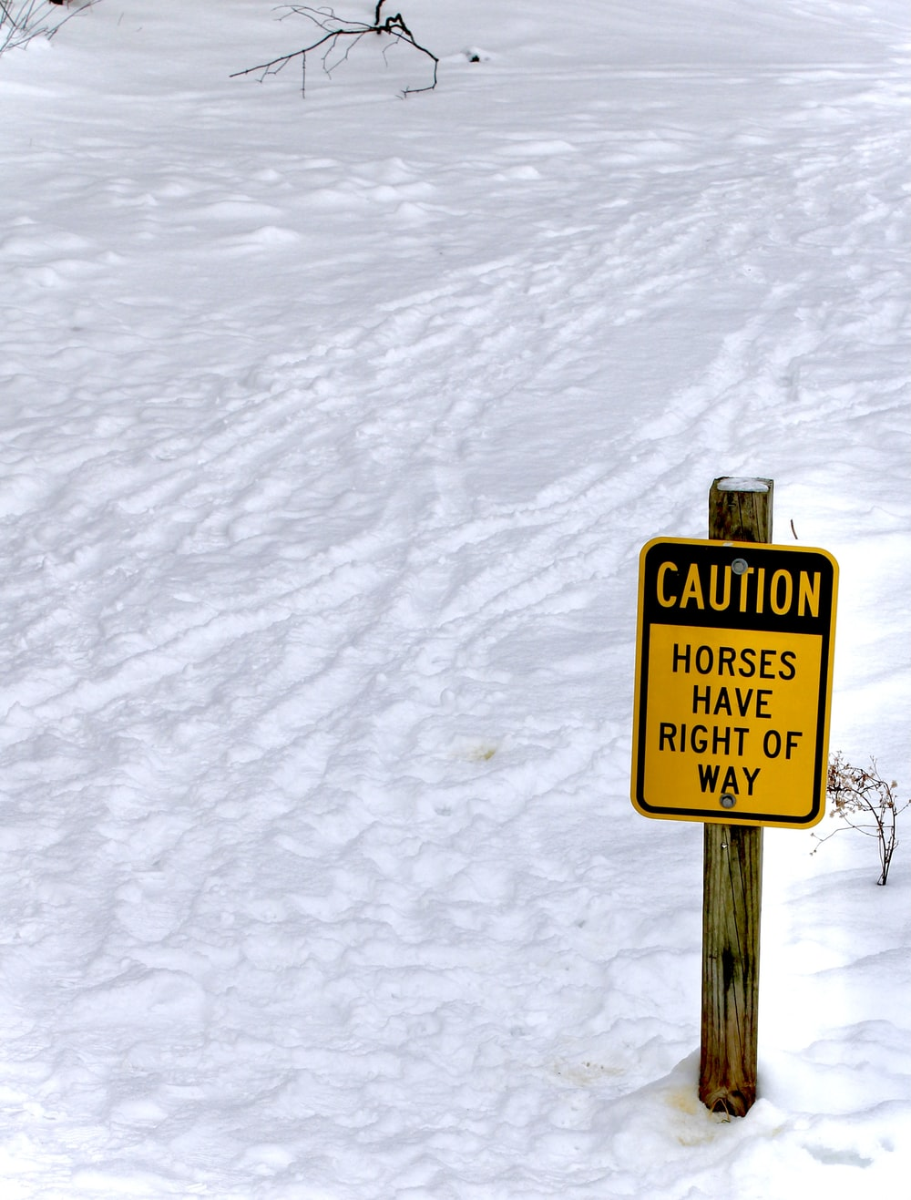 yellow and black no smoking sign on snow covered ground