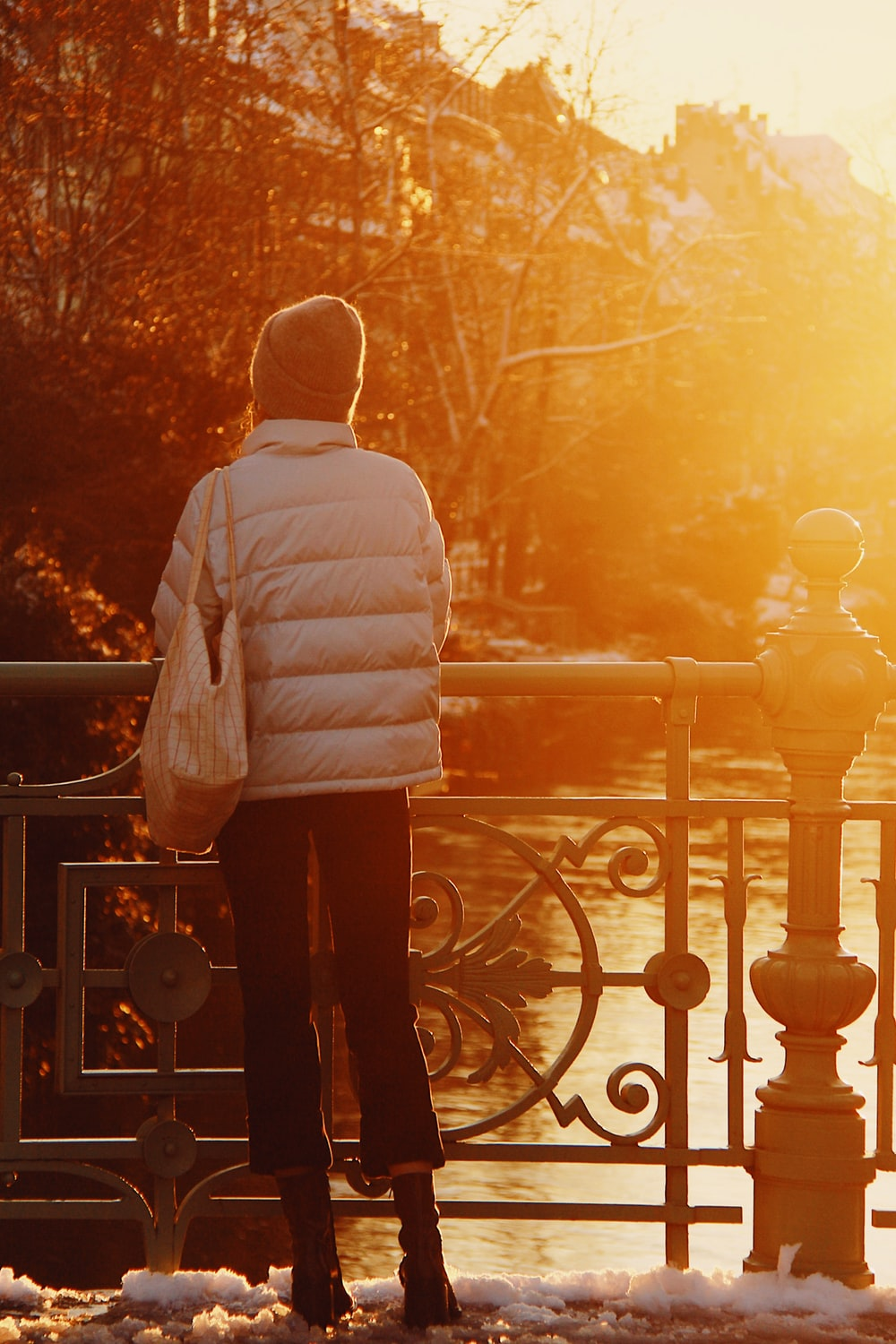 woman in white sweater standing near railings during daytime