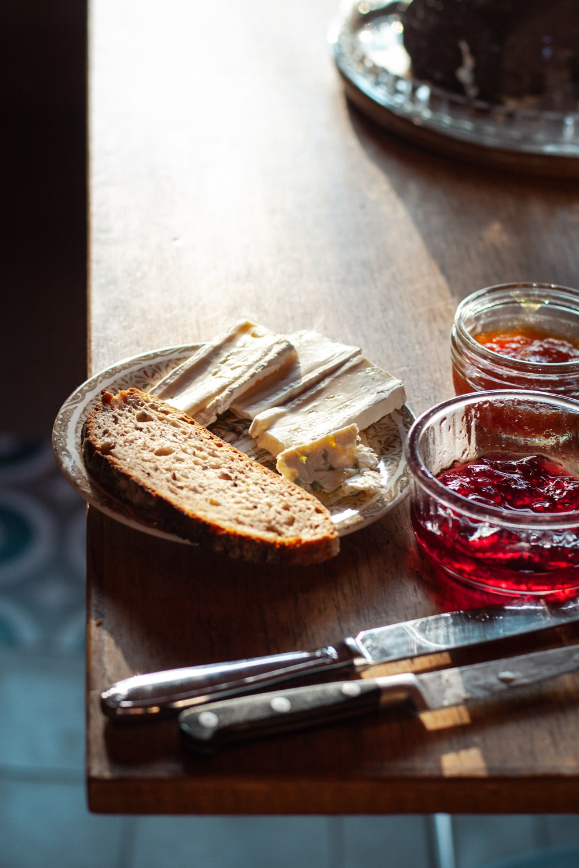 sliced bread on clear glass bowl beside stainless steel bread knife