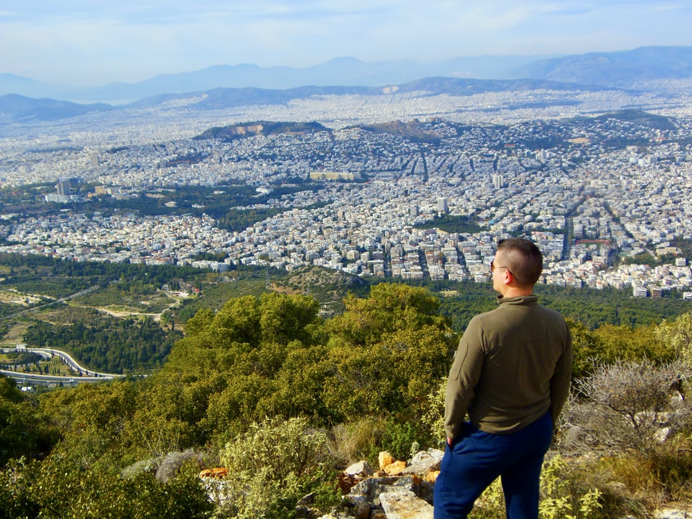 man in green long sleeve shirt standing on top of mountain looking at city during daytime