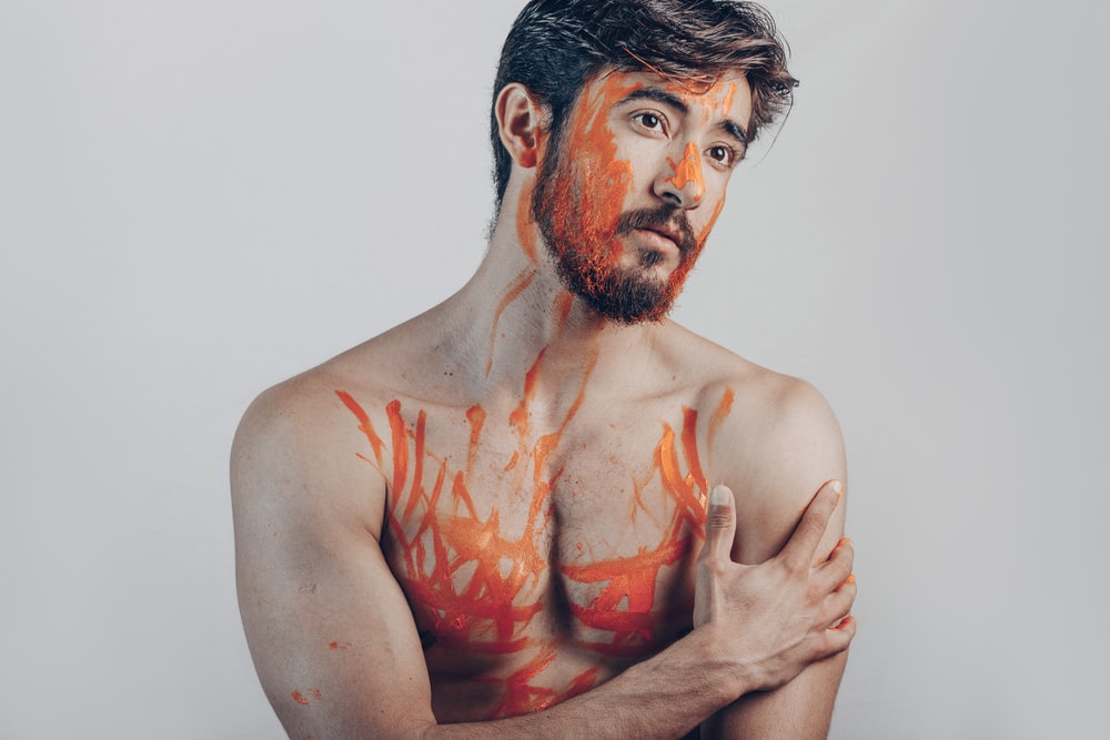 topless man with red paint on his face