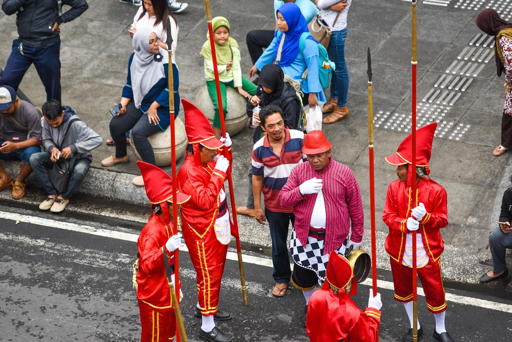 group of people in red and blue traditional dress walking on street during daytime