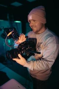 man in white crew neck long sleeve shirt holding black dslr camera