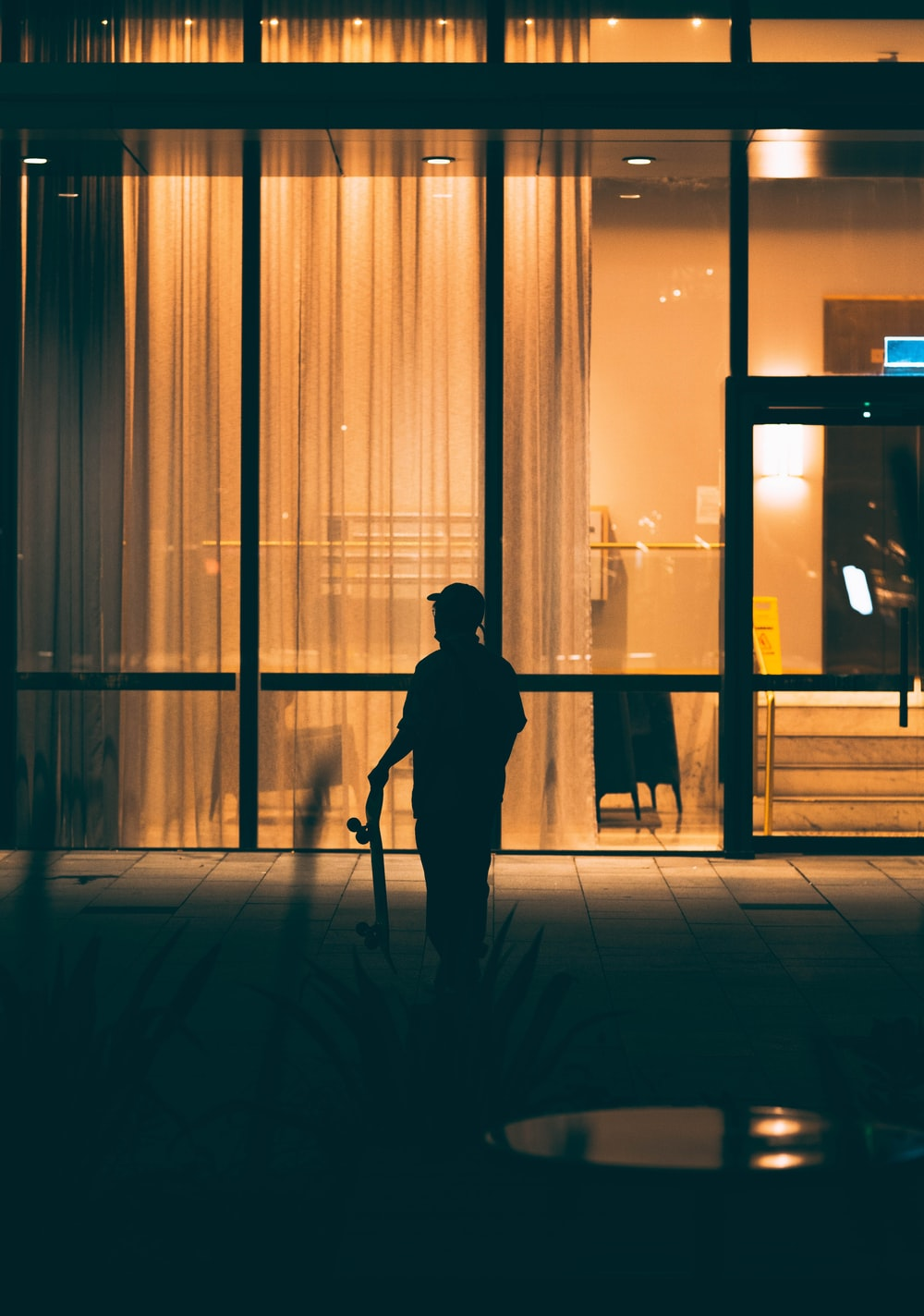 silhouette of man standing in front of glass window