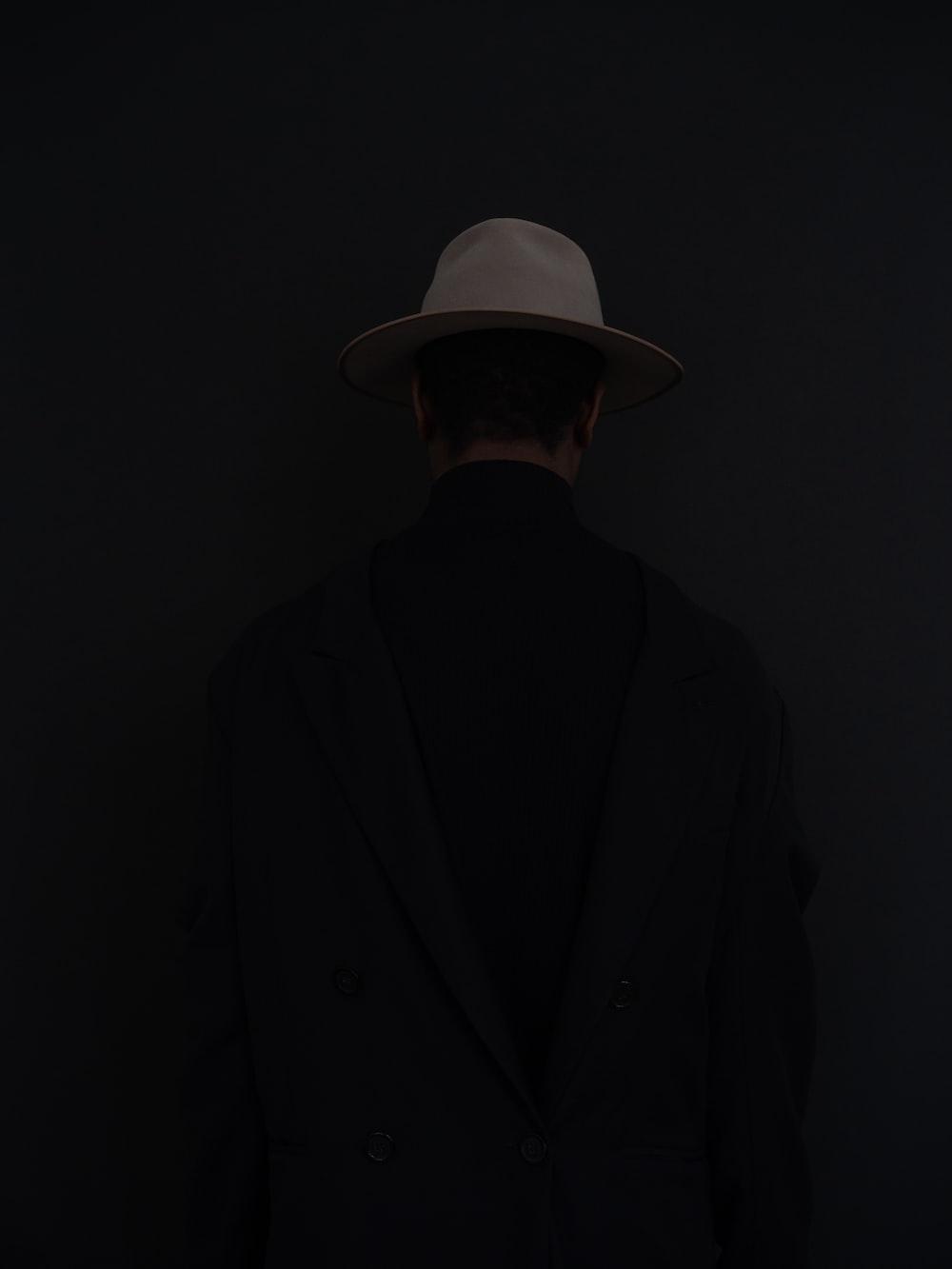 man in black suit wearing white fedora hat