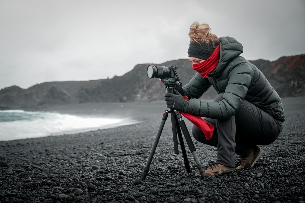 person in gray jacket and gray pants holding black dslr camera