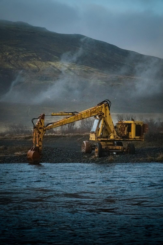 yellow excavator on water near mountain