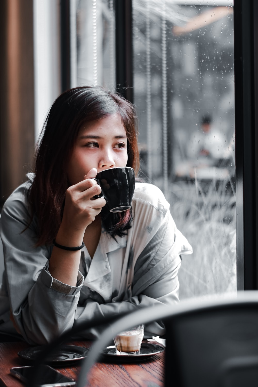 woman in white long sleeve shirt holding black ceramic mug