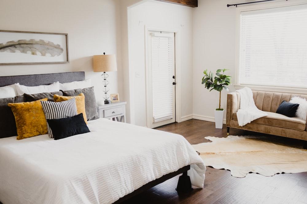 white bed linen near white wooden door