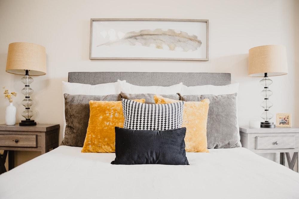 白いベッドに黒と白の枕を投げる