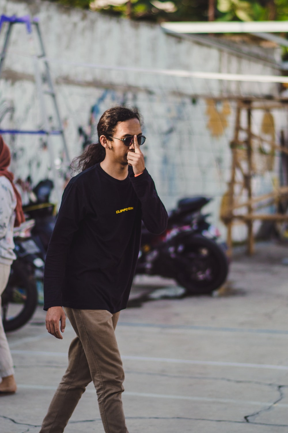 man in black crew neck t-shirt and brown pants wearing black sunglasses standing on gray