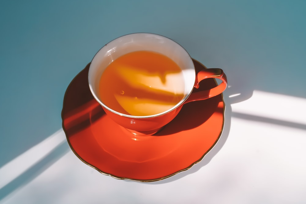 red ceramic teacup on red saucer