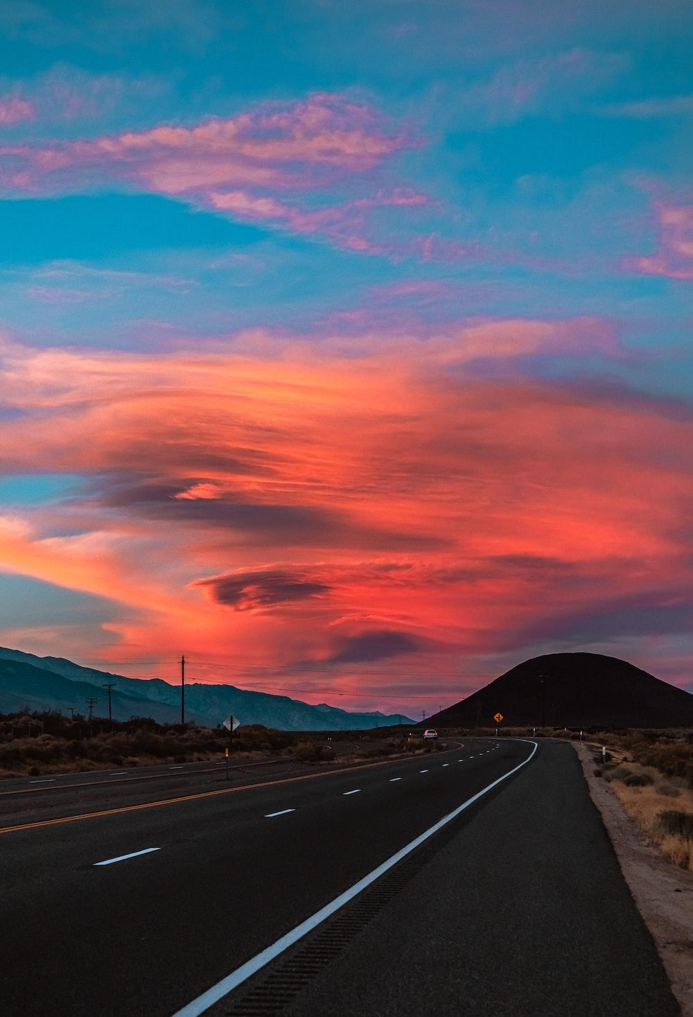 gray asphalt road under orange and blue sky