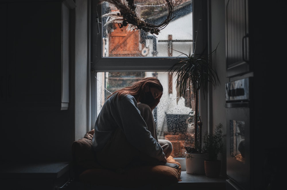 woman in gray long sleeve shirt sitting on window during daytime
