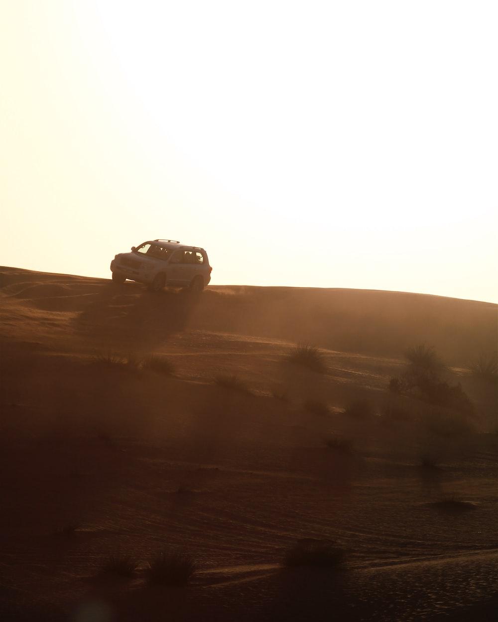 silhouette of car on desert during daytime