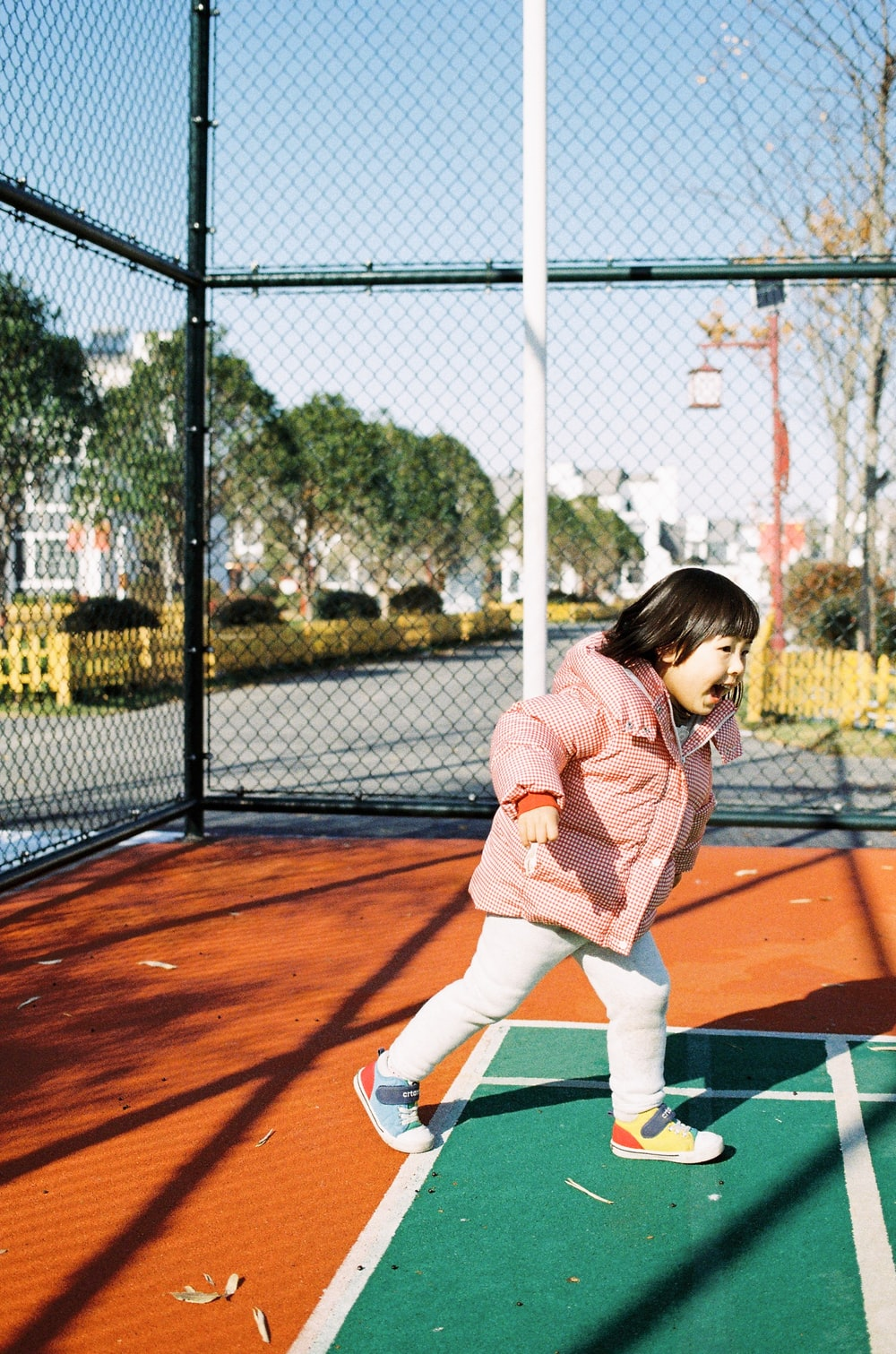 girl in pink jacket and white pants playing tennis during daytime