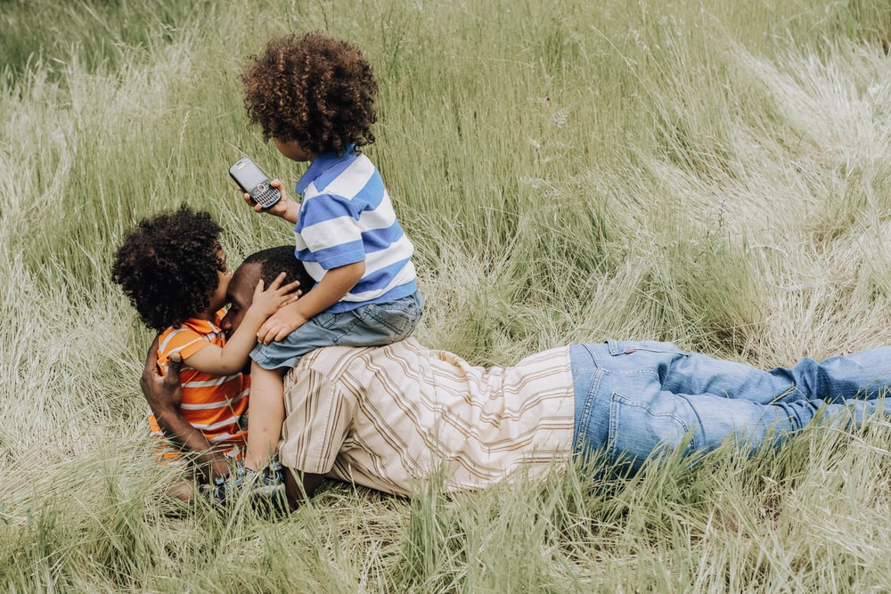 man and woman sitting on grass field during daytime