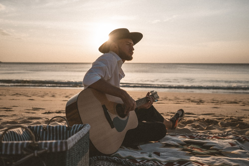 man in white dress shirt and brown cowboy hat playing acoustic guitar on beach during daytime