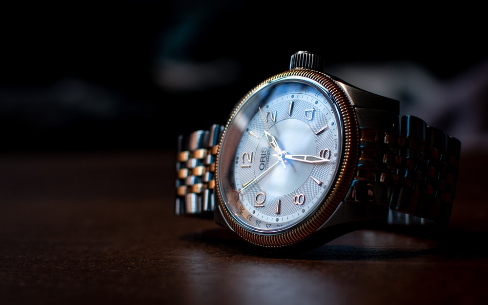 silver and blue analog watch at 10 10
