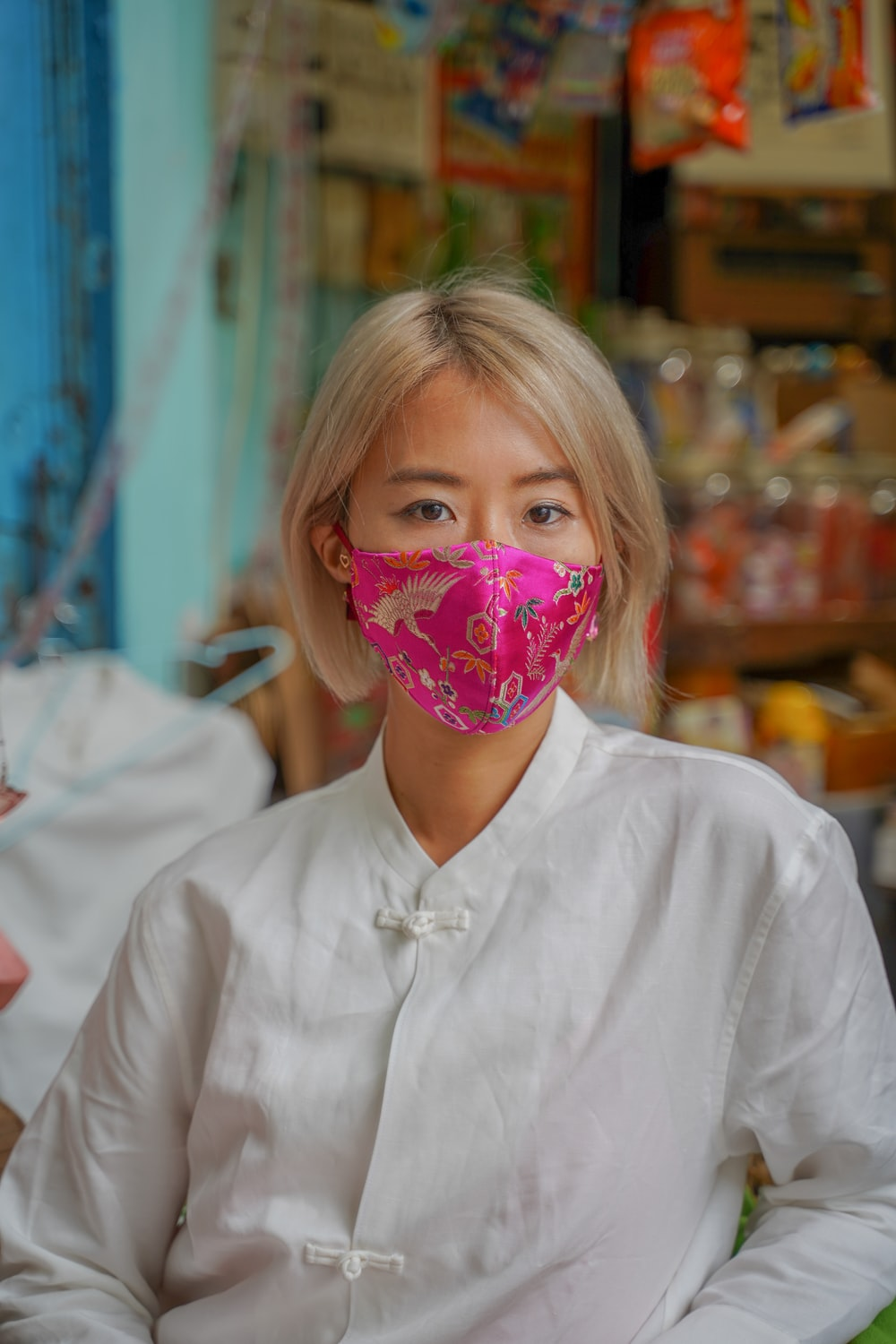 girl in white button up shirt with pink and white floral mask