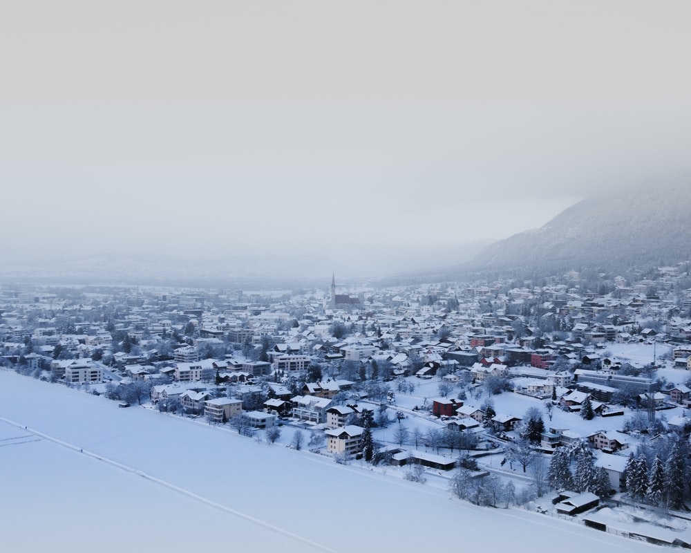 white and black houses on snow covered mountain during daytime