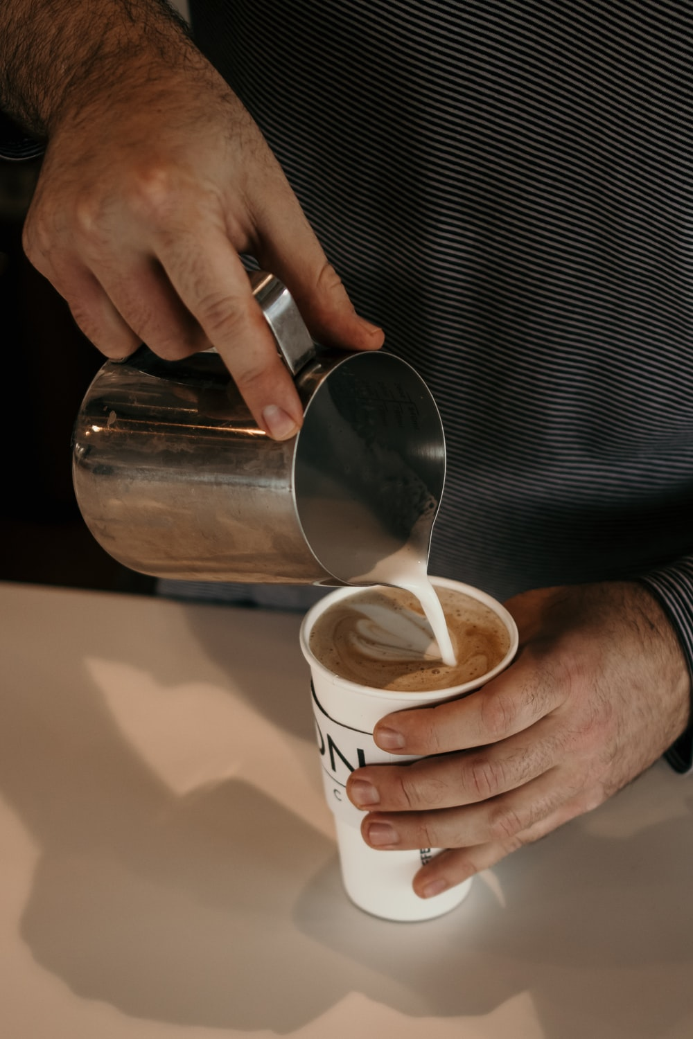 person holding stainless steel cup with white liquid