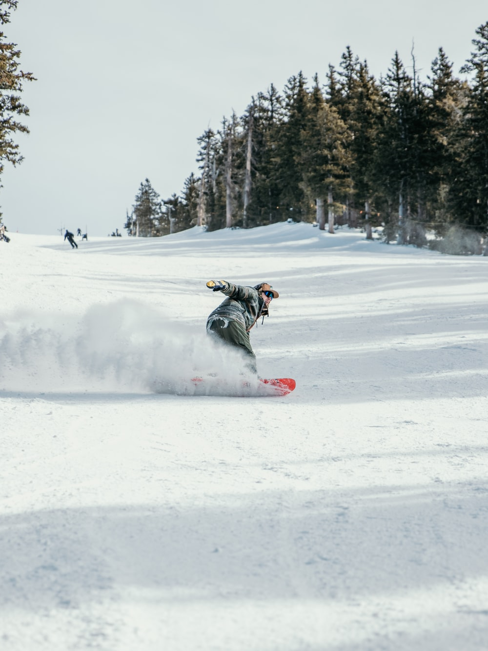 person in black jacket riding on snowboard during daytime