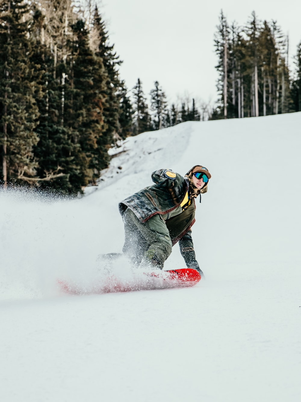 person in black and white jacket riding red snowboard on snow covered ground during daytime