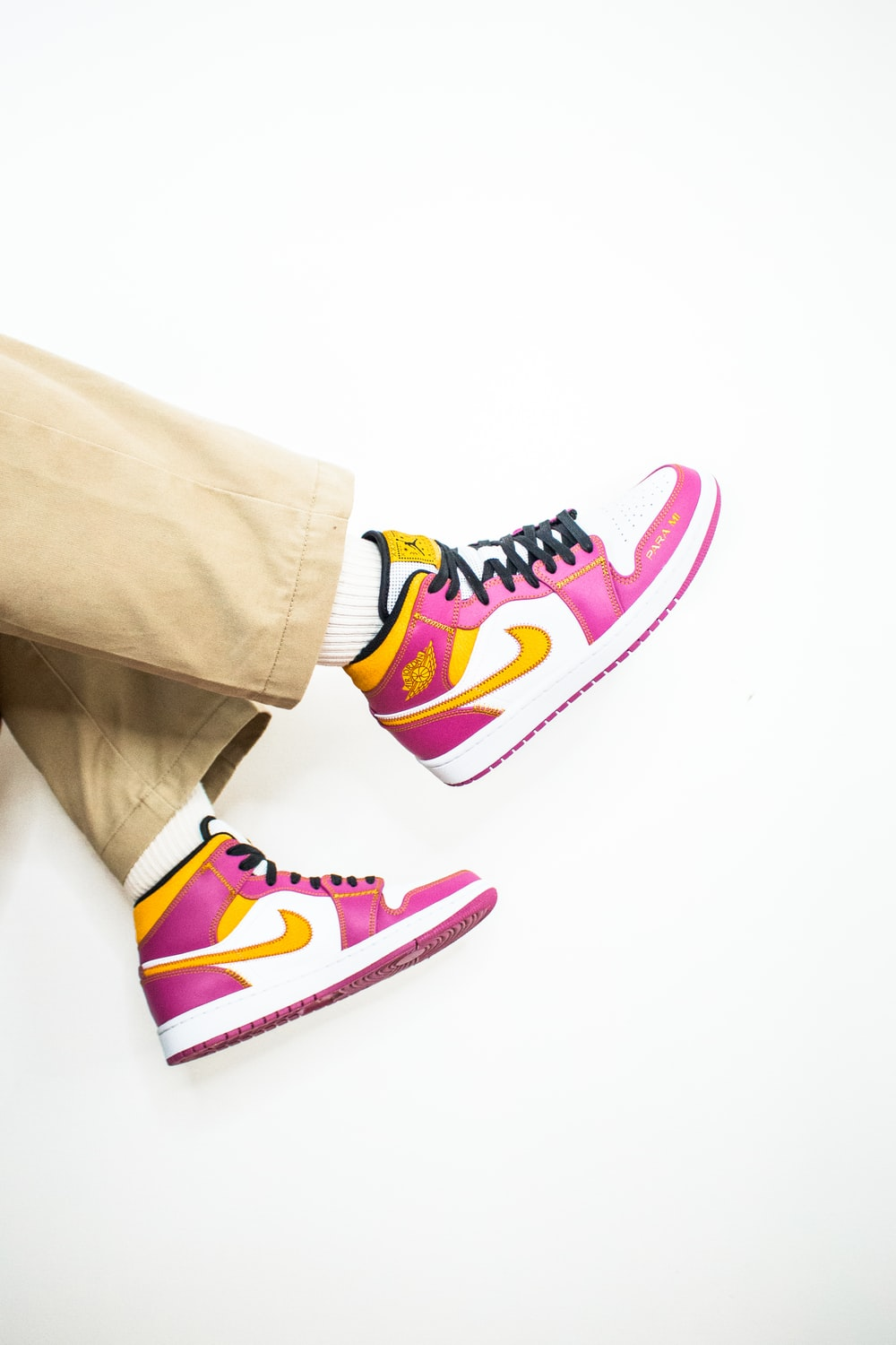 person in brown pants and blue white and pink nike sneakers